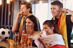 Groupe d'amis observant le football dans le bar Images stock
