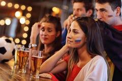 Groupe d'amis observant le football dans le bar Images libres de droits