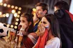 Groupe d'amis observant le football dans le bar Photographie stock