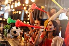 Groupe d'amis observant le football dans le bar Image libre de droits