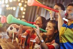 Groupe d'amis observant le football dans le bar Photos libres de droits