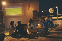 Groupe d'amis observant le football sur un dessus de toit de bâtiment photographie stock libre de droits