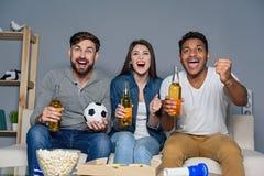 Groupe d'amis observant le sport ensemble Image libre de droits