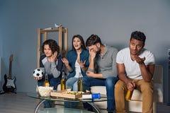 Groupe d'amis observant le sport ensemble Photos libres de droits