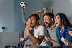 Groupe d'amis observant le sport ensemble Images libres de droits