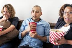Groupe d'amis observant un film d'horreur Images stock