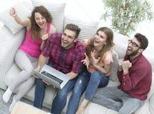 Groupe d'amis observant une vidéo sur un ordinateur portable et rire Image libre de droits