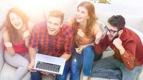 Groupe d'amis observant une vidéo sur un ordinateur portable et rire Photo libre de droits