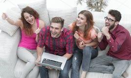 Groupe d'amis observant une vidéo sur un ordinateur portable et rire Image stock
