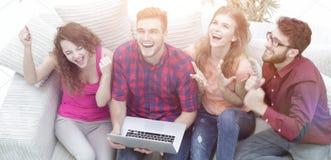 Groupe d'amis observant une vidéo sur un ordinateur portable et rire Images stock
