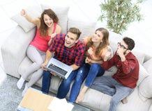 Groupe d'amis observant une vidéo sur un ordinateur portable et rire Photo stock