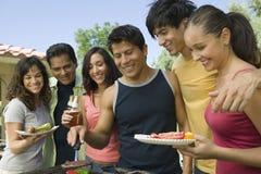 Groupe d'amis occasionnels appréciant un barbecue Images libres de droits