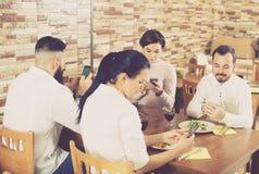 Groupe d'amis occupés à l'aide des smartphones au restaurant Image stock