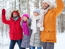 Groupe d'amis ondulant des mains dans la forêt d'hiver Photographie stock libre de droits