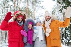 Groupe d'amis ondulant des mains dans la forêt d'hiver Image libre de droits