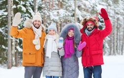 Groupe d'amis ondulant des mains dans la forêt d'hiver Photos stock