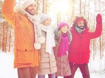 Groupe d'amis ondulant des mains dans la forêt d'hiver Images stock
