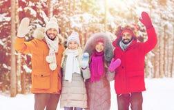 Groupe d'amis ondulant des mains dans la forêt d'hiver Image stock