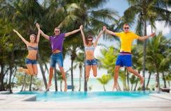 Groupe d'amis ou de couples sautant sur la plage Photographie stock