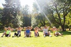 Groupe d'amis ou de sportifs s'exerçant dehors Photo stock