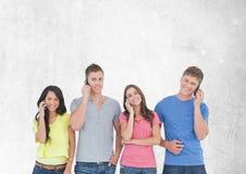 Groupe d'amis parlant aux téléphones devant le fond gris vide Photographie stock
