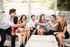 Groupe d'amis parlant et ayant des boissons Photographie stock