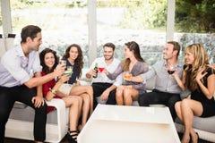 Groupe d'amis parlant et ayant des boissons Images libres de droits