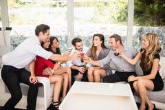 Groupe d'amis parlant et ayant des boissons Images stock