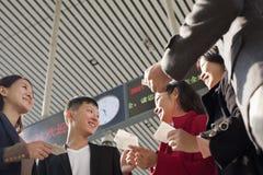 Groupe d'amis parlant et regardant des billets la gare ferroviaire Photos stock