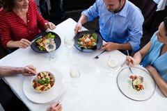Groupe d'amis parlant tout en prenant le déjeuner Photographie stock libre de droits