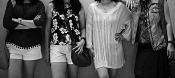 Groupe d'amis posant ensemble à l'arrière-plan noir et blanc photographie stock libre de droits