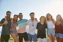 Groupe d'amis posant ensemble rire d'extérieur Photo stock