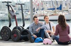 Groupe d'amis posant près des segways sur le rivage Image stock