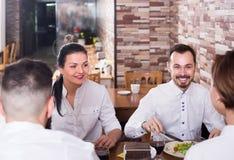 Groupe d'amis positifs mangeant au restaurant et à la causerie Photos libres de droits