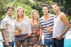 Groupe d'amis préparant le barbecue près de la piscine Photo libre de droits