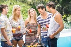 Groupe d'amis préparant le barbecue près de la piscine Image libre de droits