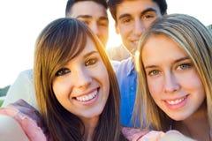 Groupe d'amis prenant des photos avec un smartphone Images libres de droits