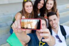 Groupe d'amis prenant des photos avec un smartphone dans la rue Photographie stock libre de droits