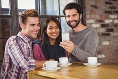 Groupe d'amis prenant des selfies avec un smartphone Image libre de droits