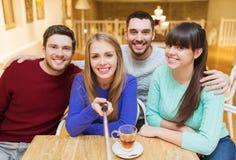 Groupe d'amis prenant la photo avec le bâton de selfie Image stock