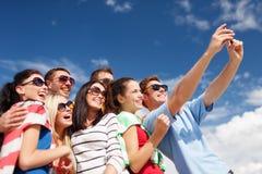 Groupe d'amis prenant la photo avec le smartphone Photos libres de droits