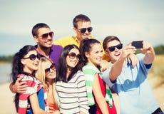 Groupe d'amis prenant la photo avec le smartphone Photo libre de droits