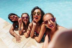 Groupe d'amis prenant la photo de selfie dans la piscine Image libre de droits
