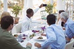 Groupe d'amis prenant le selfie au téléphone portable pendant le déjeuner Image libre de droits