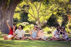 Groupe d'amis prenant le selfie avec le téléphone portable Photographie stock libre de droits