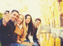 Groupe d'amis prenant le selfie en parc d'automne Photographie stock libre de droits
