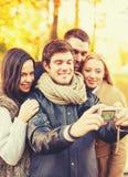 Groupe d'amis prenant le selfie en parc d'automne Images libres de droits