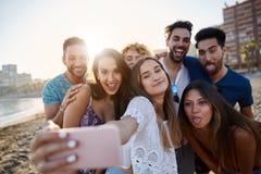 Groupe d'amis prenant le selfie ensemble sur la plage Photographie stock