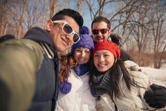 Groupe d'amis prenant un selfie dans la neige en hiver Photographie stock