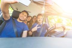 Groupe d'amis prenant un selfie dans la voiture Photo stock